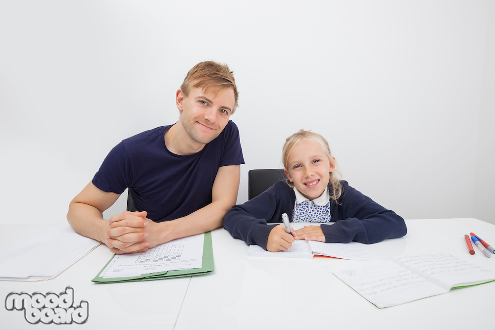 Portrait of mid adult man sitting with daughter studying at table