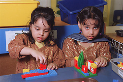 Two nursery school girls sitting at desk in classroom playing with lego,