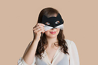 Young woman looking through eye mask over colored background