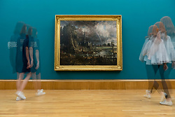 "© Licensed to London News Pictures. 25/05/2018. LONDON, UK. Staff members view ""Salisbury Cathedral from the Meadow"", 1831, by John Constable at the preview of Fire and Water, a display of masterpieces by Constable and Turner at Tate Britain.  On display for the first time in 180 years alongside each other are ""Salisbury Cathedral from the Meadow"", 1831, by John Constable and ""Caligula's Palace and Bridge"", 1831, by J.M.W. Turner.  The works will on display 26 May 208 to July 2019.  Photo credit: Stephen Chung/LNP"