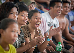 © Licensed to London News Pictures. Philippines. 24/11/2013.  Philippine boxing legend Manny Pacquiao punched his way to victory on Sunday in a match broadcast in the typhoon-ravaged city of Tacloban to try to boost morale in a region still struggling to recover from the country's most devastating typhoon.  Close to 4,000 people crowded around 40-inch-televisions and small projector screens at the Tacloban City Convention Centre, locally known as the astrodome.  Photo credit: Alison Baskerville/LNP