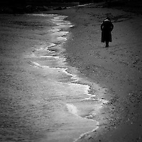 A lone woman dressed in a long black coat walking along the shore line of the Pacific Ocean.