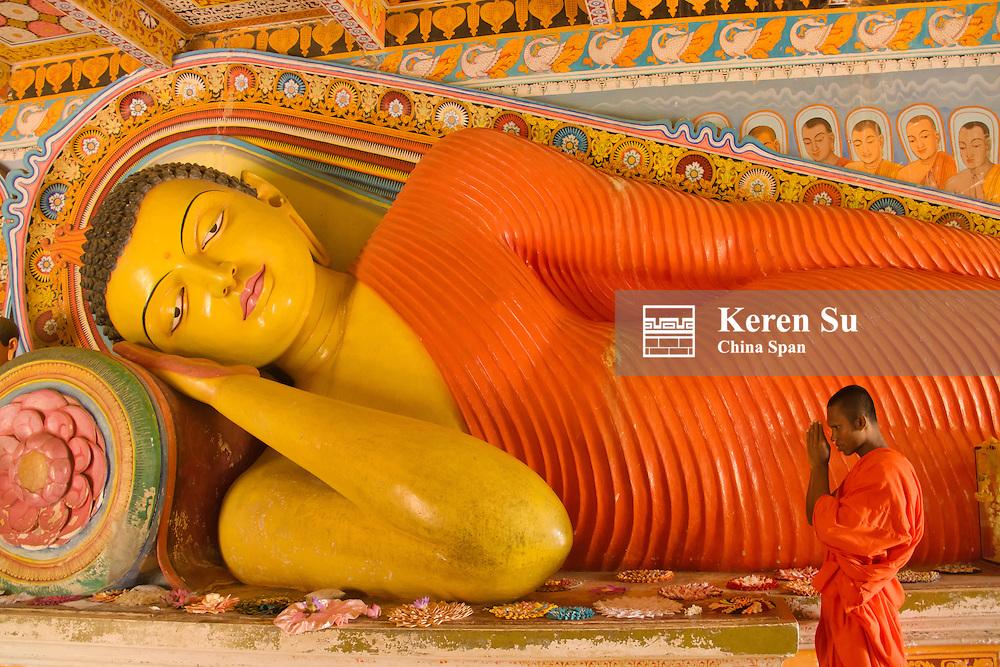 Monk praying at Reclining Buddha at Isunumuni Raja Hama Viharaya, Anuradhapura (UNESCO World Heritage site), Sri Lanka