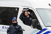Brussels 23 March 2016 female police officers at subway maalbeek keep watch. One of them had something in her eye or she adjusted her contact lens, and uses the side mirror of the car to fetch it