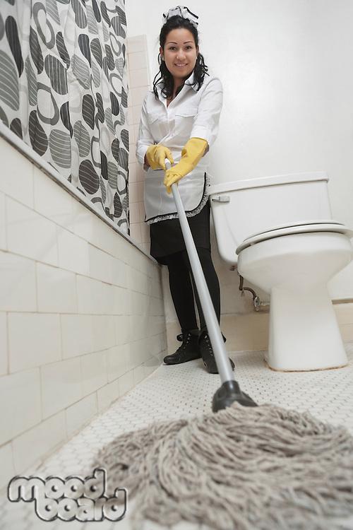 Full length portrait of maidservant cleaning bathroom floor