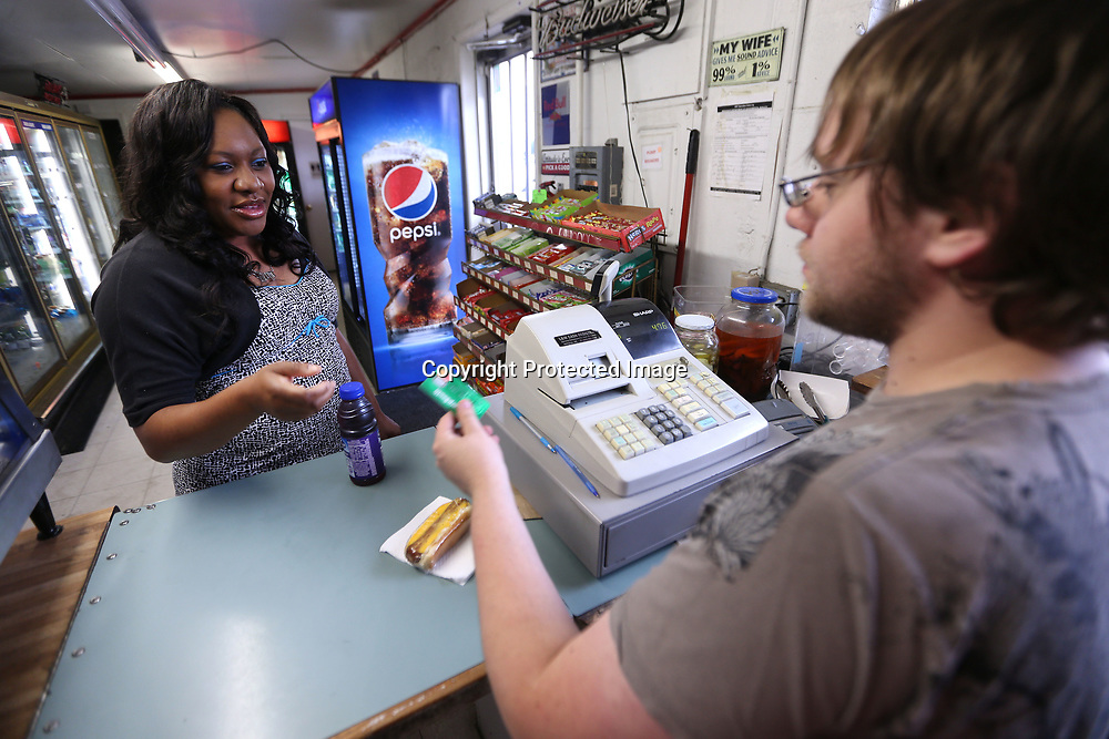 Ashley Jones, of Tupelo, pays, James Sharp, for her breakfast as she stops at the Local Express convenience store on her way to her job with the municipal courts in Tupelo. The Local Express serves hot food daily and is located on Green Street in Tupelo.