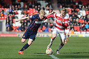 Blackpool forward Mark Cullen (9) goes past Doncaster Rovers Craig Alcock (38)  during the Sky Bet League 1 match between Doncaster Rovers and Blackpool at the Keepmoat Stadium, Doncaster, England on 28 March 2016. Photo by Simon Davies.