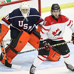 COBOURG, - Dec 15, 2015 -  Game #5 - Canada West vs the United States at the 2015 World Junior A Challenge at the Cobourg Community Centre, ON. Kris Oldham #30 of Team United States and Justin Fregona #14 of Team Canada West during the first period.(Photo: Tim Bates / OJHL Images)