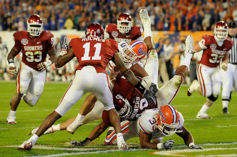 January 8, 2009: Lendy Holmes and Mike Balogun of the Oklahoma Sooners tackle Tim Tebow of the Florida Gators during the NCAA football game between the Florida Gators and the Oklahoma Sooners in the 2009 BCS National Championship Game. The Gators defeated the Sooners 24-14.