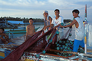 fishermen load their nets into <br /> the panga in preparation for the <br /> night's fishing, Malapascua Island, <br /> off Cebu, Philippines