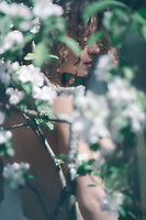 Romantic sensual portrait of a beautiful nude young woman behind white flowers of apple blossom outdoors in spring in soft green colors