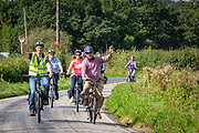 The front two men of a cycling group wave whilst travelling along Cradducks Lane country road in Staplehurst, Kent, England, UK.  (photo by Andrew Aitchison / In pictures via Getty Images)