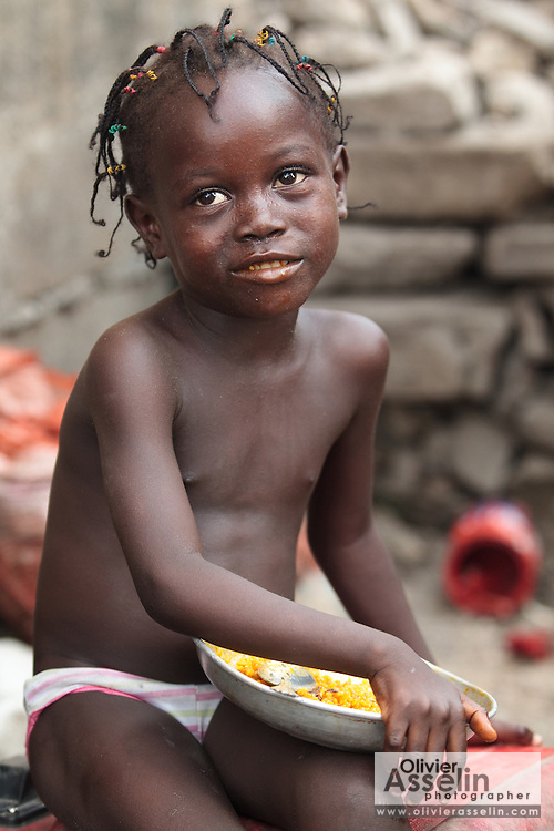 A girl eats from a plate of rice in the West Point slum of Monrovia, Montserrado county, Liberia on Monday April 2, 2012.