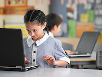 Elementary schoolgirl using laptop in classroom