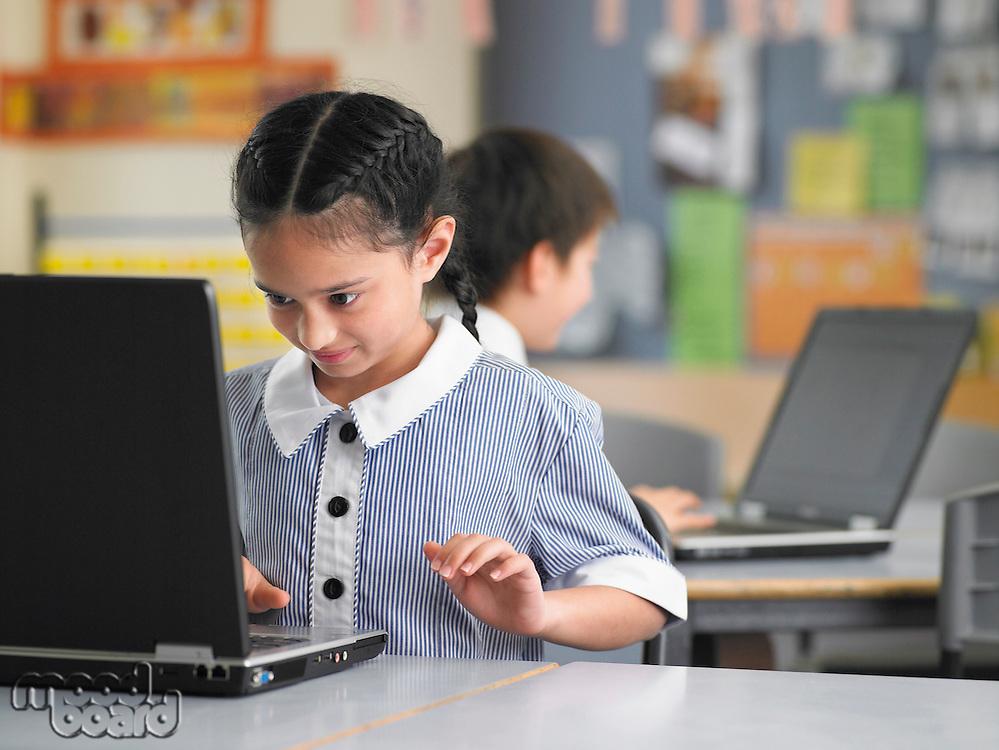 Elementary schoolgirl using laptop in classroom