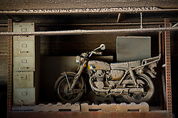 A vintage motorcycle is covered in saw dust inside of the Bono Saw Dust Supply Company, a family-owned operation for three generations.