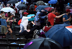 Despite heavy rainfall and low attendance some in the crowds form a congo-line to keep the spirits high during the July 4th, 2016 Wawa Welcome America concert, on the Benjamin Franklin Parkway, in Center City, Philadelphia, Pennsylvania.