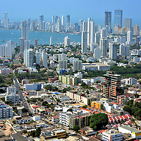 Panoramic View of High-rises in Cartagena, Colombia <br /> This panoramic view of Cartagena from Convent de la Popa shows its very modern cityscape. There are about 150 high-rises and skyscrapers. The majority have been built since 2003, especially in the Bocagrande neighborhood in the background. Most of them are condominiums to house the population of about 900,000 people. Several are luxury hotels with lots more planned. The towers in the middle stand on Manga Island. Some real estate experts have compared Cartagena's construction boom to Panama City and Miami.