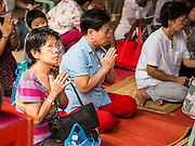 "10 AUGUST 2014 - BANGKOK, THAILAND: Women pray during a Ghost Month service to venerate ancestors at Wat Mangkon Kamalawat, the largest Mahayana Buddhist temple in Bangkok's Chinatown. The seventh month of the Chinese Lunar calendar is called ""Ghost Month"" during which ghosts and spirits, including those of the deceased ancestors, come out from the lower realm. It is common for Chinese people to make merit during the month by burning ""hell money"" and presenting food to the ghosts.      PHOTO BY JACK KURTZ"