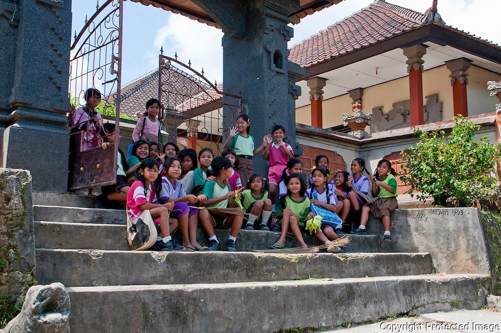 Group photo of happy schoolgirls sitting on the school steps on Nusa Penida, Bali, Indonesia