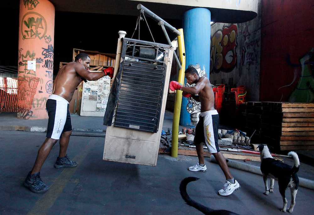 "Aspiring boxers Chibata (L) and Valdir Aparecido (nicknamed ""Gorilla"") punch a discarded refrigerator during a training session at a gymnasium under the Alcantara Machado viaduct in the Mooca neighborhood of Sao Paulo, March 28, 2011. The Boxing Academy of Garrido, founded by Brazilian former pro boxer Nilson Garrido, adopts primitive training equipment that he developed himself during his years as a coach, in a project whose goal is to take the sport to the poor and marginalized population."