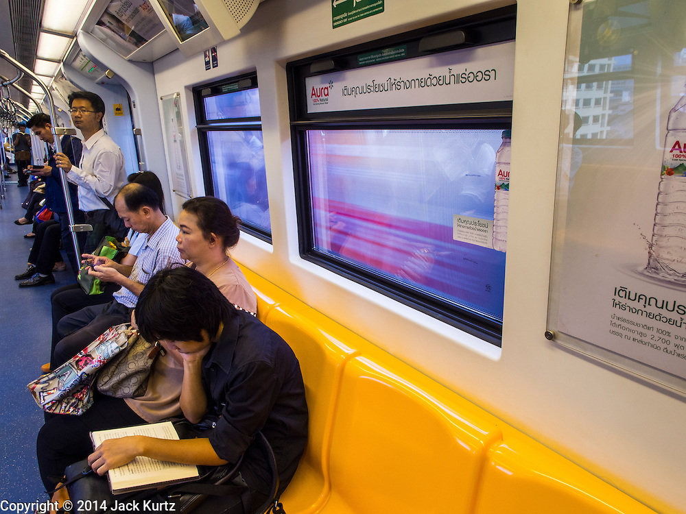 28 OCTOBER 2014 - BANGKOK, THAILAND:  Passengers on an outbound train on the Silom line of the Bangkok Skytrain. The Skytrain (called the BTS) system has a combined length of 36 kilometres and includes 34 stations, including Saphan Taksin. While there are two train tracks for most stretches of the Skytrain system, the portion on the Saphan Taksin Bridge spanning the Chao Phraya River has just one track due to limited space, causing a bottleneck when an outbound train and inbound train arrive at the bridge at the same time. The Bangkok Metropolitan Authority (BMA) had sought permission from the Department of Rural Roads to expand the Taksin Bridge in order to make way for an additional track, but the department had said it was not possible. The Saphan Taksin  station was originally supposed to be temporary and is one of the busiest on the system. It's a connecting station for the Chao Phraya River boats used by Thai commuters coming into the city from neighboring provinces and tourists who use the boats to go upriver into the old parts of Bangkok from the central business district. More than 4,000 commuters a day use the station. The BMA plans to build an elevated moving sidewalk to the river from Surasak BTS station about one kilometer away. Surasak is the nearest station to Saphan Taksin. The Skytrain system has a combined length of 36 kilometres and includes 34 stations, including Saphan Taksin.       PHOTO BY JACK KURTZ