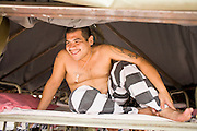 "17 JULY 2006 - PHOENIX, AZ: Inmates relax in their bunks after the National Anthem was played in ""Tent City"" in the Maricopa County Jail in Phoenix, AZ. There are about 650 inmates living in the tents. Maricopa County Sheriff Joe Arpaio recently started playing the Star Spangled Banner and God Bless America twice a day in the county jails. Inmates are encouraged, but not forced, to stand at attention with their hands over their hearts, when the music is played. When asked about the new policy Arpaio said, ""Our men and women are fighting and dying for our country in Iraq and that's the least these inmates can do."" In 2011, the US Department of Justice issued a report highly critical of the Maricopa County Sheriff's Department and the jails. The DOJ said the Sheriff's Dept. engages in widespread discrimination against Latinos during traffic stops and immigration enforcement, violates the rights of Spanish speaking prisoners in the jails and retaliates against the Sheriff's political opponents.      PHOTO BY JACK KURTZ"