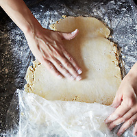 Hands beginning to roll out pie dough to make a crust.