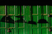 Green doors on shop with shadows of brooms at sunset