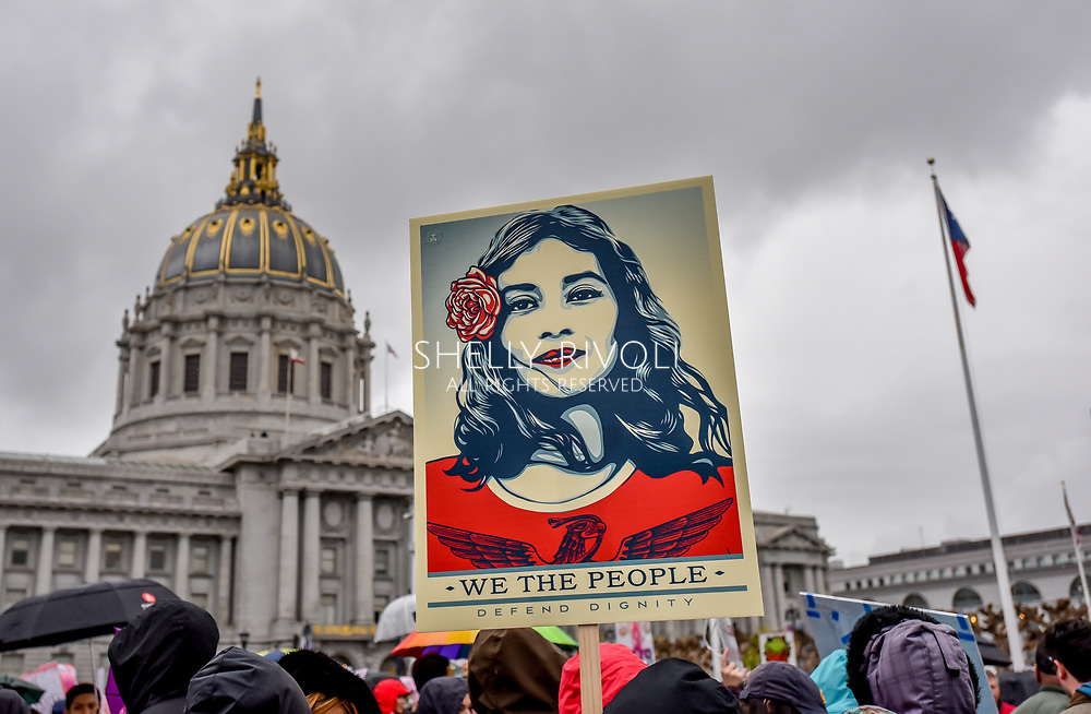 "Artist Shepard Fairey's sign ""We the People Defend Dignity,"" portraying a Latina in red, is held high in protest at the rally before San Francisco Womens March with City Hall in the background. Credit: Shelly Rivoli"
