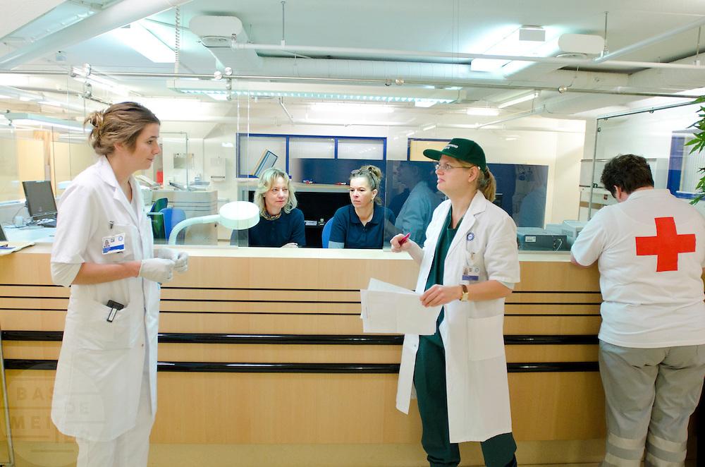 Arsten overleggen met elkaar bij de balie van de verpleegafdeling. In het Calamiteitenhospitaal in Utrecht wordt een rampenoefening gehouden. De nadruk ligt op de contaminatie, door een gekantelde vrachtwagen zijn veel slachtoffers in aanraking gekomen met een chemische stof. Voor het eerst wordt er geoefend met een zogenaamde decontaminatietent. Als de tent bevalt, schaft het ziekenhuis zo'n tent aan. Bij de 'ramp' zijn 100 slachtoffers gevallen.<br /> <br /> Doctors are having a discussion. In the Trauma and Emergency Hospital in Utrecht an calamity training was held. The emphasis is on the contamination by an overturned truck, many victims are contaminated by a chemical. For the first time a so-called decontamination tent was used. If the tent fulfills the expectations, a tent will be purchased. The 'calamity' caused 100 victims.