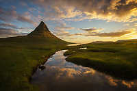 Mt Kirkjufell and clouds refelcting in a small pool of water after sunrise, Iceland