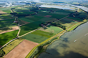 Nederland, Brabant, Gemeente Werkendam, 12-06-2009; polder Noordwaard in de Biesbosch, onderdeel van 'Ruimte voor de Rivier' (bescherming tegen hoogwater door rivierverruiming). Door het gedeeltelijke afgraven van de dijken zijn in- en uitstroomopeningen in de Merwededijk gemaakt (boven in beeld) en is een doorstroomgebied ontstaan waardoor de kans op overstromingen (in de bovenloop) kleiner is. Het deel van de polder wat nu nog landbouwgrond is, onder in beeld, zal in de toekomst ook ontpoldert worden.Polder Noordwaard (part of Biesbosch National Park), part of the program 'Space for the River' (protection against high water by means of creating space for rivers).Because the dike next to the river has been partly excaveted, entrances for the water of the river have been made (left, above middle). The former polder right of the dike can now store water and allows the river to flood more easily downstream (direction of the Northsea). These measures dimishes the risk of floods further upstream at high water in the winter.luchtfoto (toeslag); aerial photo (additional fee required)foto Siebe Swart / photo Siebe Swart