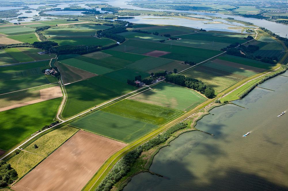 Nederland, Brabant, Gemeente Werkendam, 12-06-2009; polder Noordwaard in de Biesbosch, onderdeel van 'Ruimte voor de Rivier' (bescherming tegen hoogwater door rivierverruiming). Door het gedeeltelijke afgraven van de dijken zijn in- en uitstroomopeningen in de Merwededijk gemaakt (boven in beeld) en is een doorstroomgebied ontstaan waardoor de kans op overstromingen (in de bovenloop) kleiner is. Het deel van de polder wat nu nog landbouwgrond is, onder in beeld, zal in de toekomst ook ontpoldert worden.Polder Noordwaard (part of Biesbosch National Park), part of the program 'Space for the River' (protection against high water by means of creating space for rivers).Because the dike next to the river has been partly excaveted, entrances for the water of the river have been made (left, above middle). The former polder right of the dike can now store water and allows the river to flood more easily downstream (direction of the Northsea). These measures dimishes the risk of floods further upstream at high water in the winter.luchtfoto (toeslag); aerial photo (additional fee required)foto Siebe Swart / photo Siebe Swart