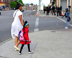 A young girl walking with her mother at the intersection of North and Pennsylvania glances at police officers dressed in tactical gear. Law enforcement officers and soldiers from the Maryland National Guard on May 1, 2015, keep a watchful eye throughout Baltimore after days of unrest following Freddie Gray's fatal injury April 12  while in police custody.