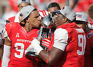 Dec 5, 2015; Houston, TX, USA; Houston Cougars defensive end Cameron Malveaux (94) and defensive lineman Nick Thurman (91) kiss the 2015 Mid-American Conference trophy after defeating the Temple Owls in the in the Mid-American Conference football championship game at TDECU Stadium. Houston won 24 to 13. Mandatory Credit: Thomas B. Shea-USA TODAY Sports