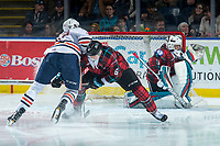 KELOWNA, CANADA - MARCH 10: Jermaine Loewen #32 of the Kamloops Blazers checks Kaedan Korczak #6 as he approaches the net of James Porter #1 of the Kelowna Rockets  on March 10, 2018 at Prospera Place in Kelowna, British Columbia, Canada.  (Photo by Marissa Baecker/Shoot the Breeze)  *** Local Caption ***