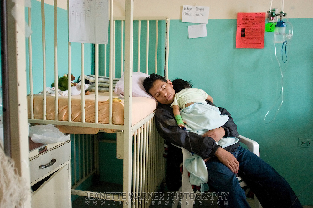 "Edgar Ortíz sleeps while holding his recouperating son.  For several days after the operation, Ortíz hardly let a moment pass when he did not have his son in his arms.  ""I never thought the day would come . . . I had lost hope that my son would be operated on.  I'm so happy, but I also hurt to see him in so much pain."" says Ortíz."