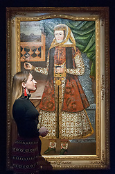 "© Licensed to London News Pictures. 20/10/2017. London, UK. A staff member views ""A Portrait of a Lady holding a rose and glass"", Persia, circa 1660-1700, (Est. GBP0.8-1.0m), at a preview of Islamic, Middle Eastern and other artworks which be auctioned at Sotheby's New Bond Street on 24 and 25 October. Photo credit : Stephen Chung/LNP"