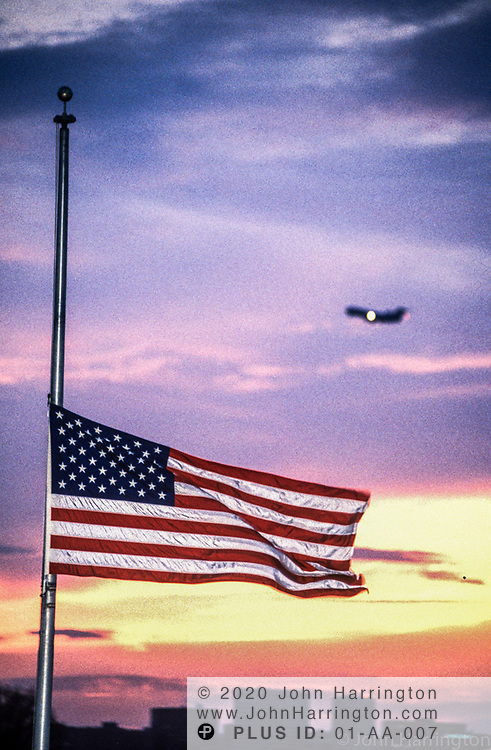 A flag at the Washington Monument flys at half mast as a plane passes by in the background.