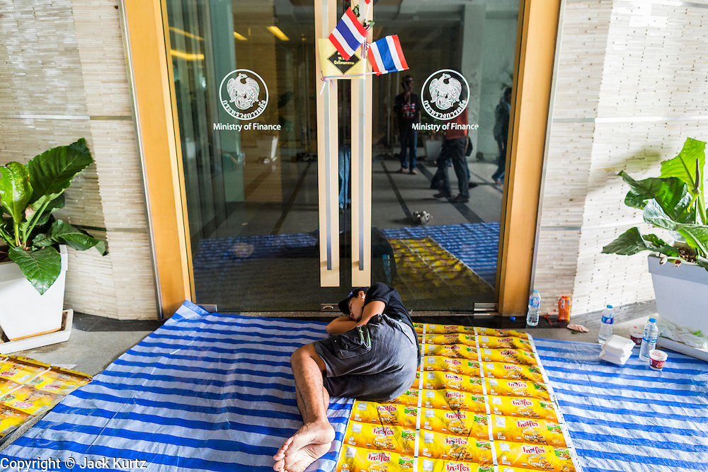 A Thai anti-government protestor sleeps in front of the Ministry of FInance.  Protestors opposed to the government of Thai Prime Minister Yingluck Shinawatra spread out through Bangkok this week. Protestors have taken over the Ministry of Finance, Ministry of Sports and Tourism, Ministry of the Interior and other smaller ministries. The protestors are demanding the Prime Minister resign, the Prime Minister said she will not step down. This is the worst political turmoil in Thailand since 2010 when 90 civilians were killed in an army crackdown against Red Shirt protestors. The Pheu Thai party, supported by the Red Shirts, won the 2011 election and now govern. The protestors demanding the Prime Minister step down are related to the Yellow Shirt protestors that closed airports in Thailand in 2008.