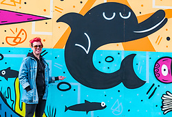 Edinburgh, Scotland, 03 May 2019. Pictured: Mural artist Katie Guthrie at the Edinburgh Dog & Cat Home mural unveiling with her favourite section. The 80 foot mural is unveiled today as a colourful addition to Seafield promenade. It is designed and painted by local artists Studio N_Name. It depicts the people, heritage and environment of the local community and features flora, fauna and historic elements of the local coastline. It has been made possible through through partnership with Edinburgh Shoreline Project. It is on the seafront wall of the dog & cat home which rescues, reunites and rehomes lost, stray and abandoned dogs and cats across Edinburgh and the Lothians, caring for 2,367 dogs and 771 cats in 2018.<br /> Sally Anderson | EdinburghElitemedia.co.uk