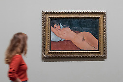 "© Licensed to London News Pictures. 21/11/2017. London, UK.  A staff member walks by ""Reclining Nude on a White Cushion"", 1917. Preview of ""Modigliani"", the most comprehensive exhibition of works by Amedeo Modigliani ever held in the UK.  On display are iconic portraits, sculptures and 12 nudes, the largest group ever shown in the UK.  The show runs 23 November to 2 April 2018.  Photo credit: Stephen Chung/LNP"