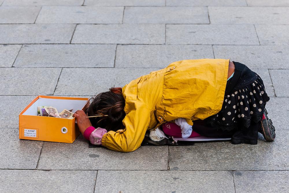 Girl begging on the sidewalk, Beijing Middle Road, Lhasa, Tibet (Xizang), China.