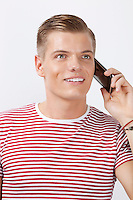 Happy young man using cell phone against white background