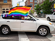 "28 JUNE 2020 - DES MOINES, IOWA: A motorist participates in the Capitol City Pride Parade in Des Moines. Most of the Pride Month events in Des Moines were cancelled this year because of the COVID-19 pandemic, but members of the Des Moines LGBTQI community, and Capitol City Pride, the organization that coordinates Pride Month events, organized a community ""parade"" of people driving through the East Village of Des Moines displaying gay pride banners and flags. About 75 cars participated in the parade.     PHOTO BY JACK KURTZ"