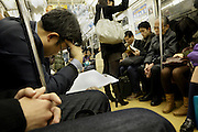 businessman reading paperwork while commuting Tokyo Japan