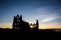 © Licensed to London News Pictures. 01/10/2015. Whitby, UK. Picture shows Whitby Abbey in last nights sunset. The fishing town of Whitby awoke to a thick covering of fog but the weather is due to brighten up later today. Photo credit: Andrew McCaren/LNP