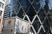 As heatwave temperatures climb to record levels - the hottest day of the year so far - the workplace in the City of London (the capital's financial district aka the Square Mile) appears on a van on St. Mary Axe, beneath the Swiss re 'Gherkin' building, on 25th July 2019, in London, England.
