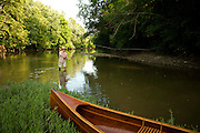 A fly fisherman casts for smallmouth bass on the Olentangy River in Central Ohio.  His handmade wooden canoe is seen in the foreground.
